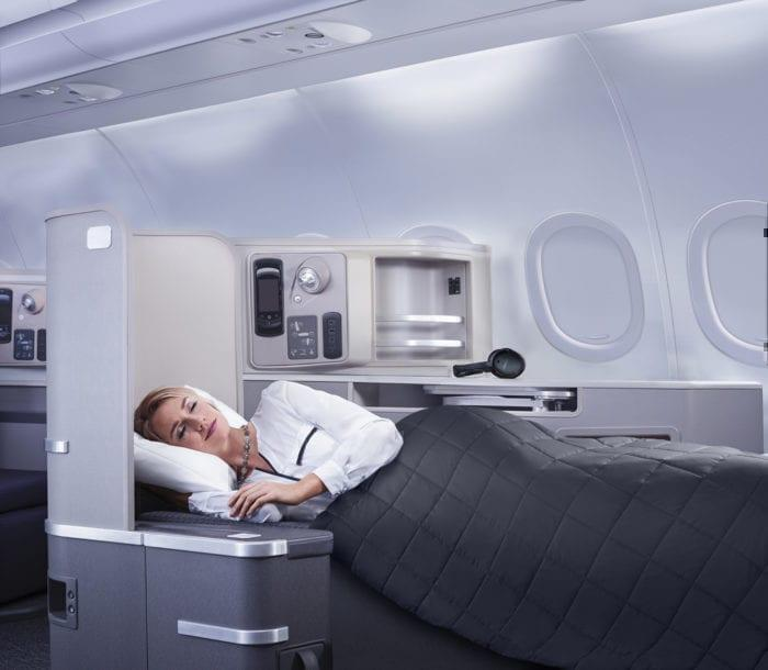 A weary passenger sleeps on a night flight.