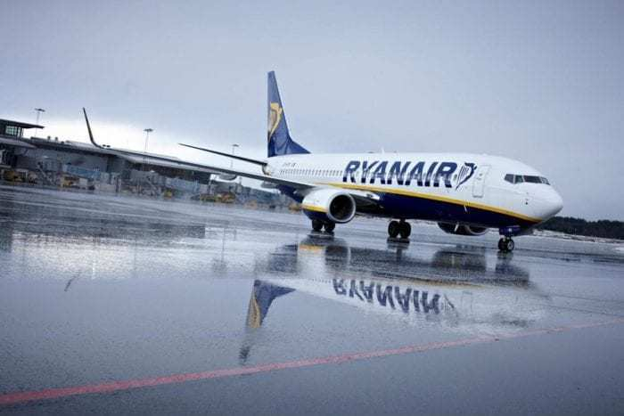 Ryanair airliner on apron in rain