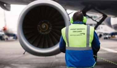 Ground crew sits in front of plane engine
