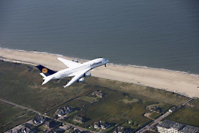 Lufthansa A380 in flight over beach