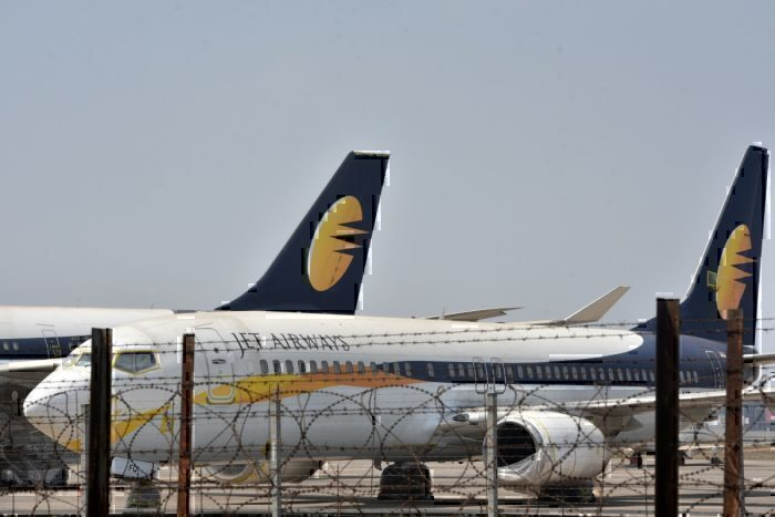Jet airways aircraft at airport behind barbed wire fence