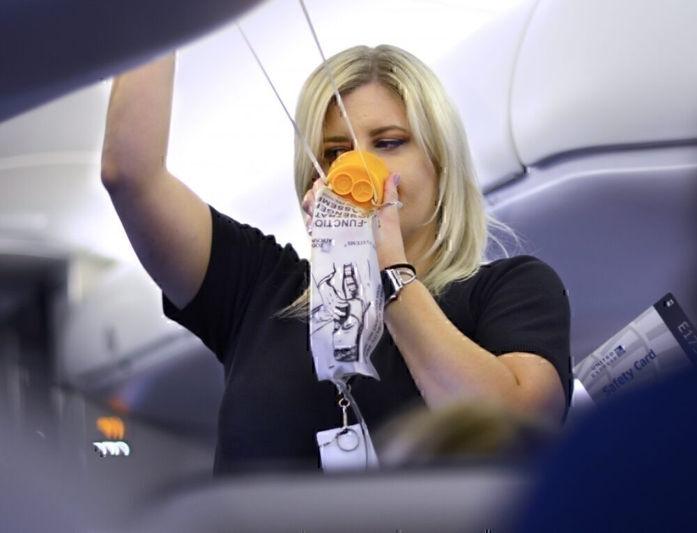 united cabin crew demonstrates mask