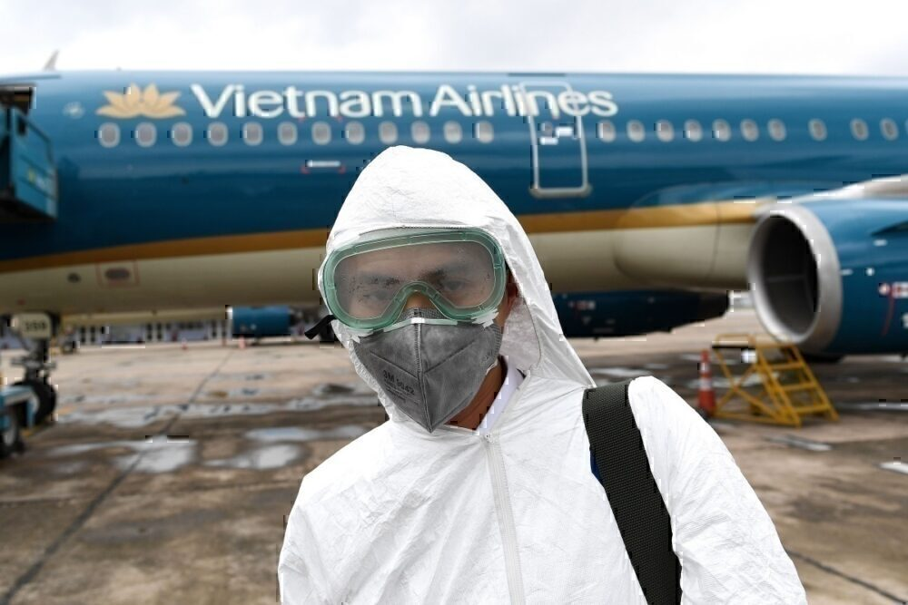 Vietnam airlines worker in mask disinfecting plane
