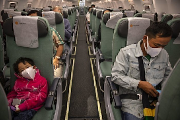 Father and son wearing masks on a plane during the coronavirus outbreak