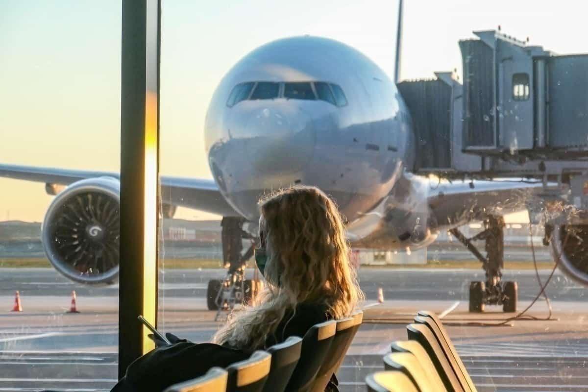 woman waits to board aircraft at airport