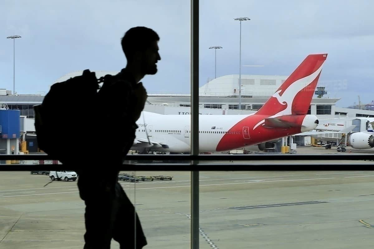 Passenger walks near Qantas flight