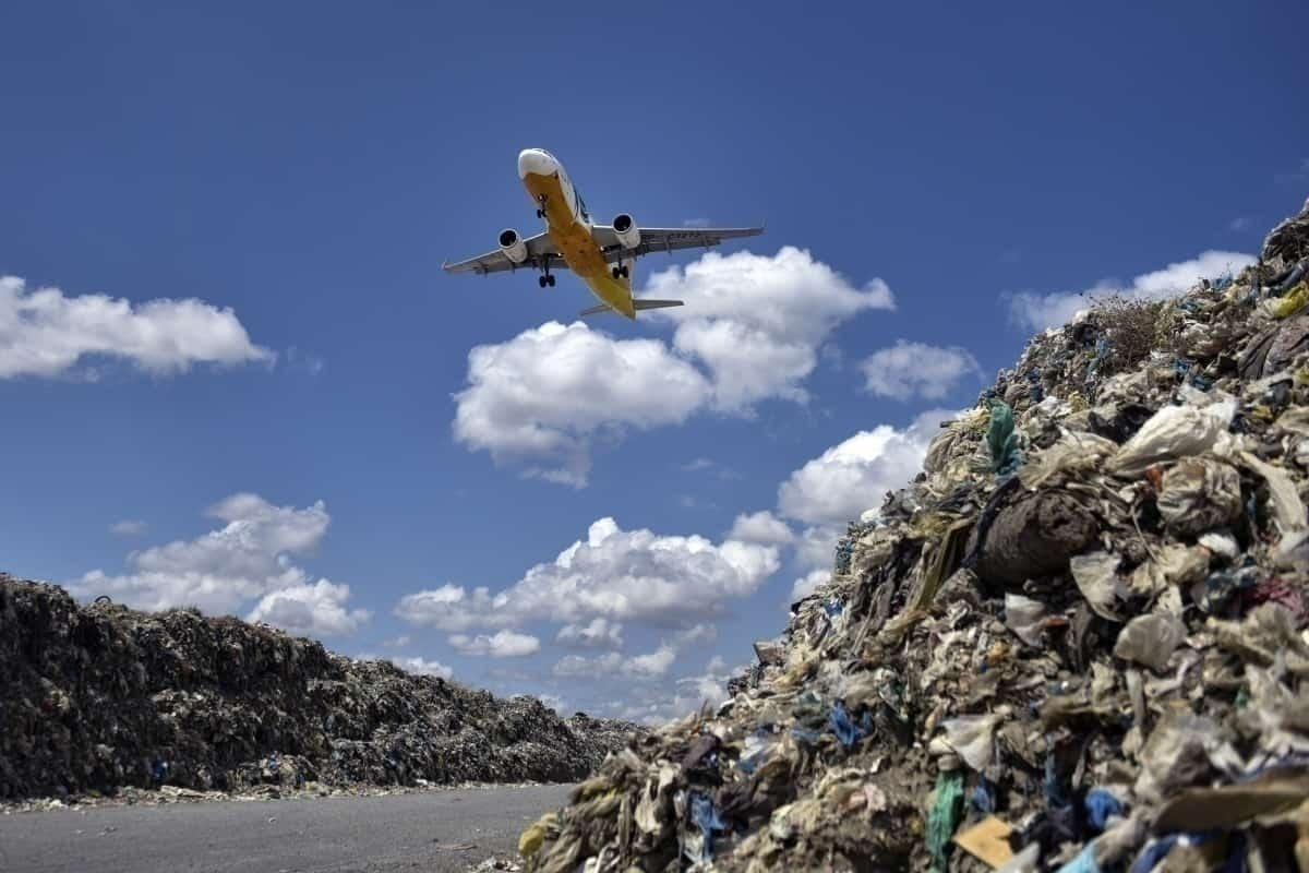 plane flies over landfill