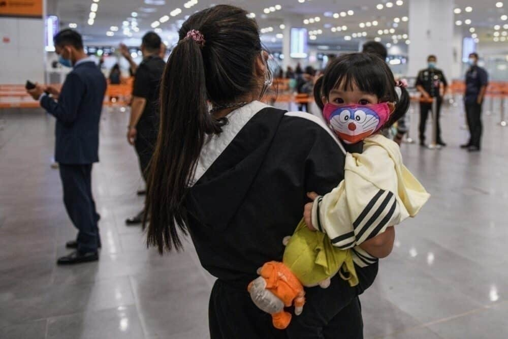 Woman holds daughter with mask in Malaysia