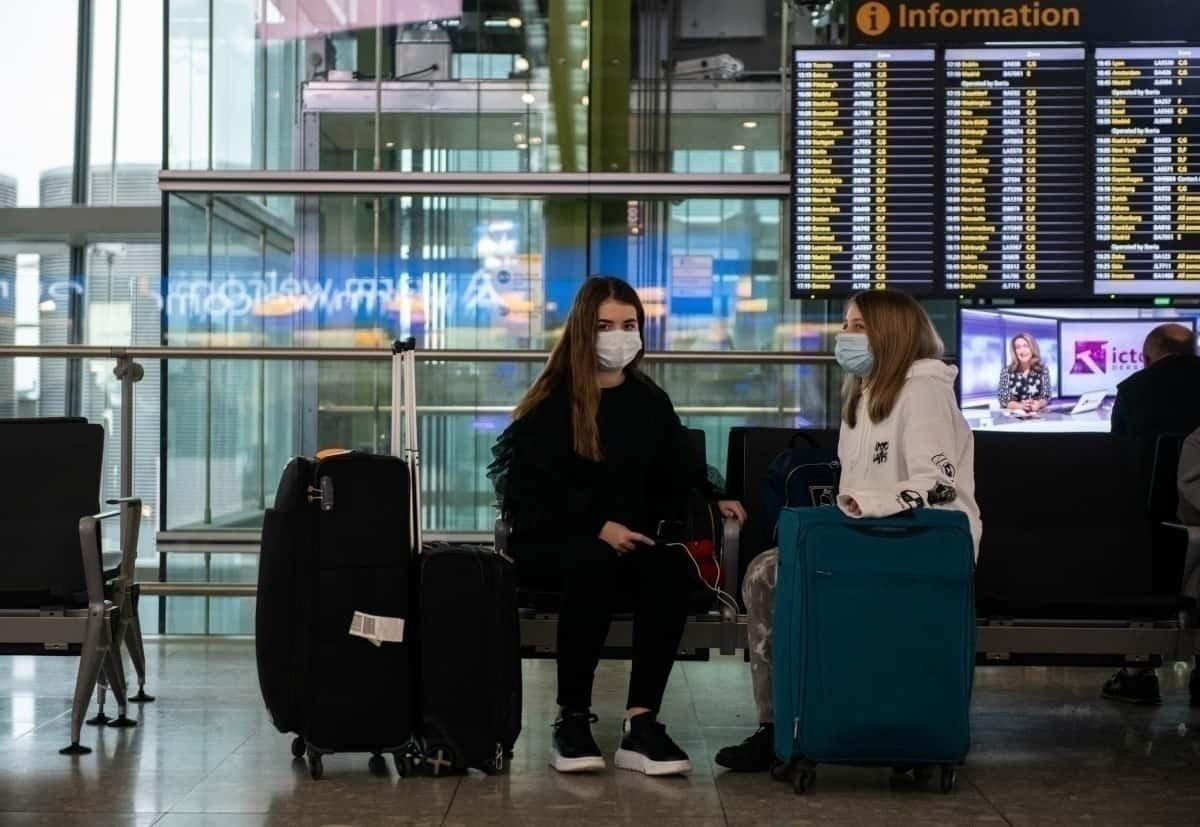 2 women sit in airport with masks on