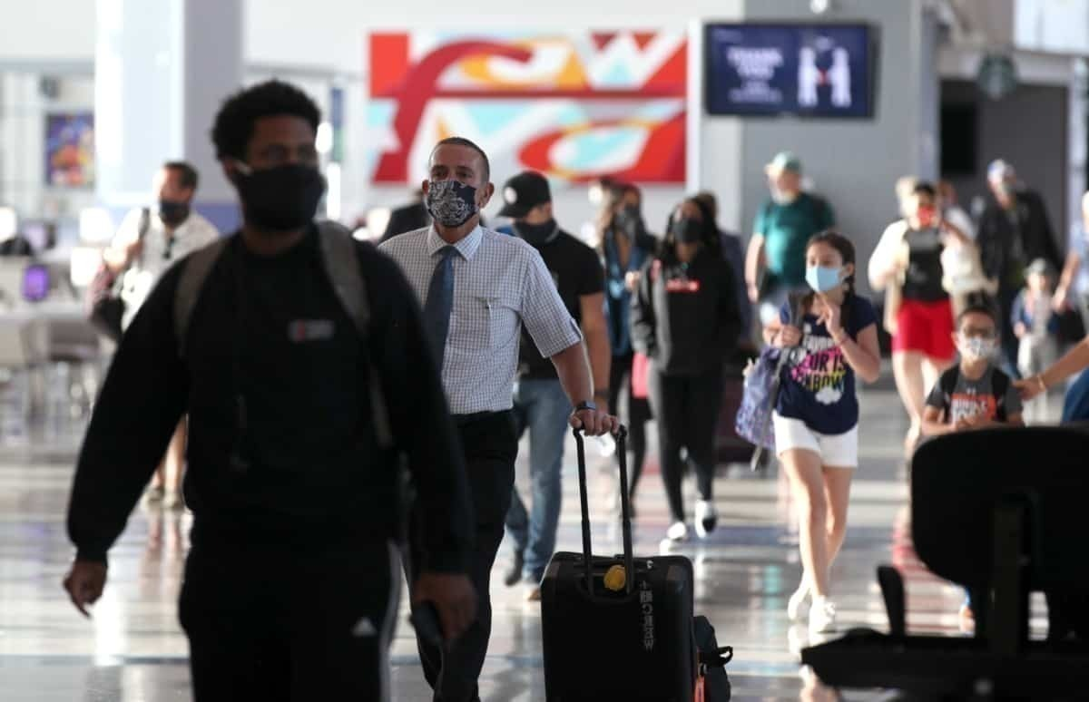 Busy airport, passengers with masks