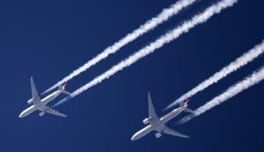 2 commercial jets fly with contrails