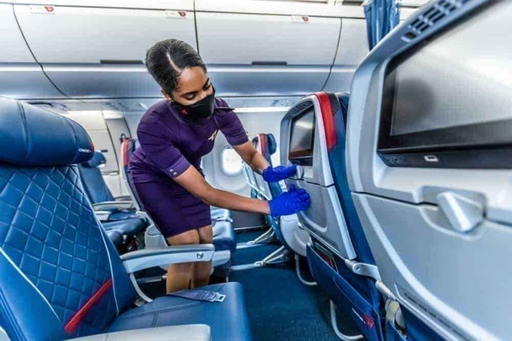 Delta staff member cleans aircraft