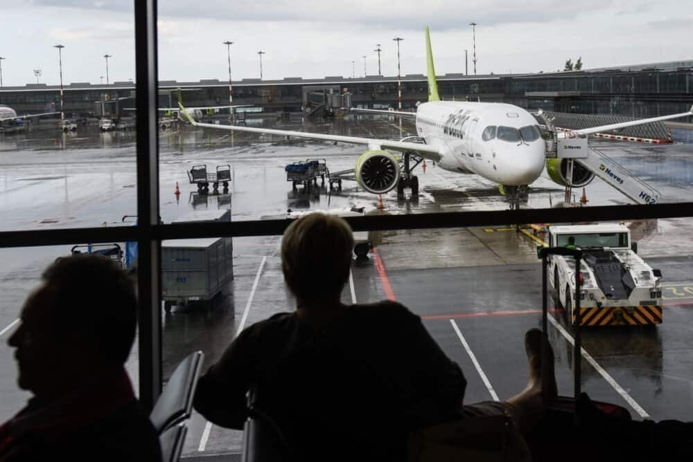 passengers watch A220-300 airBaltic at Riga International