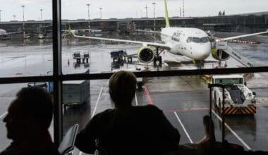 passengers watch A220-300 airBaltic at Riga International
