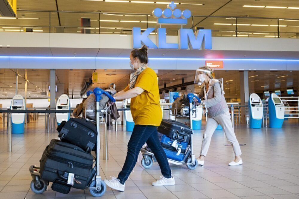 Travelers wearing a face mask walk by KLM check-in