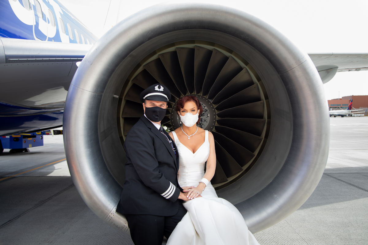 A bride and groom sit in the engine of a Boeing 737