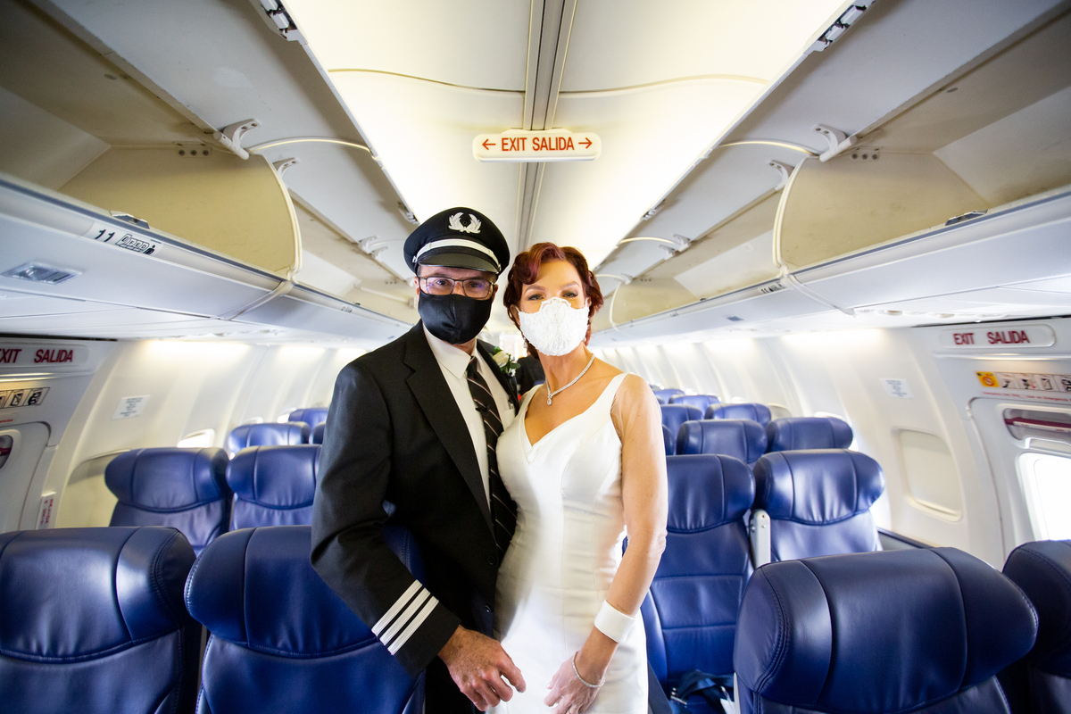 A bride and groom stand in the aisle of a Boeing 737