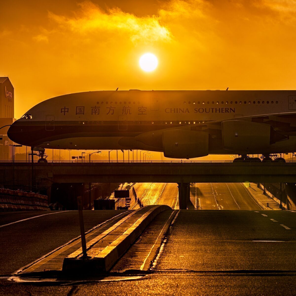 China southern A380 crosses a bridge in front of the setting sun