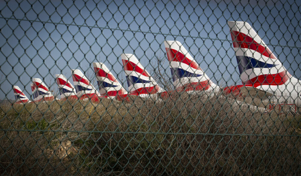 British Airways planes parked behind a fence