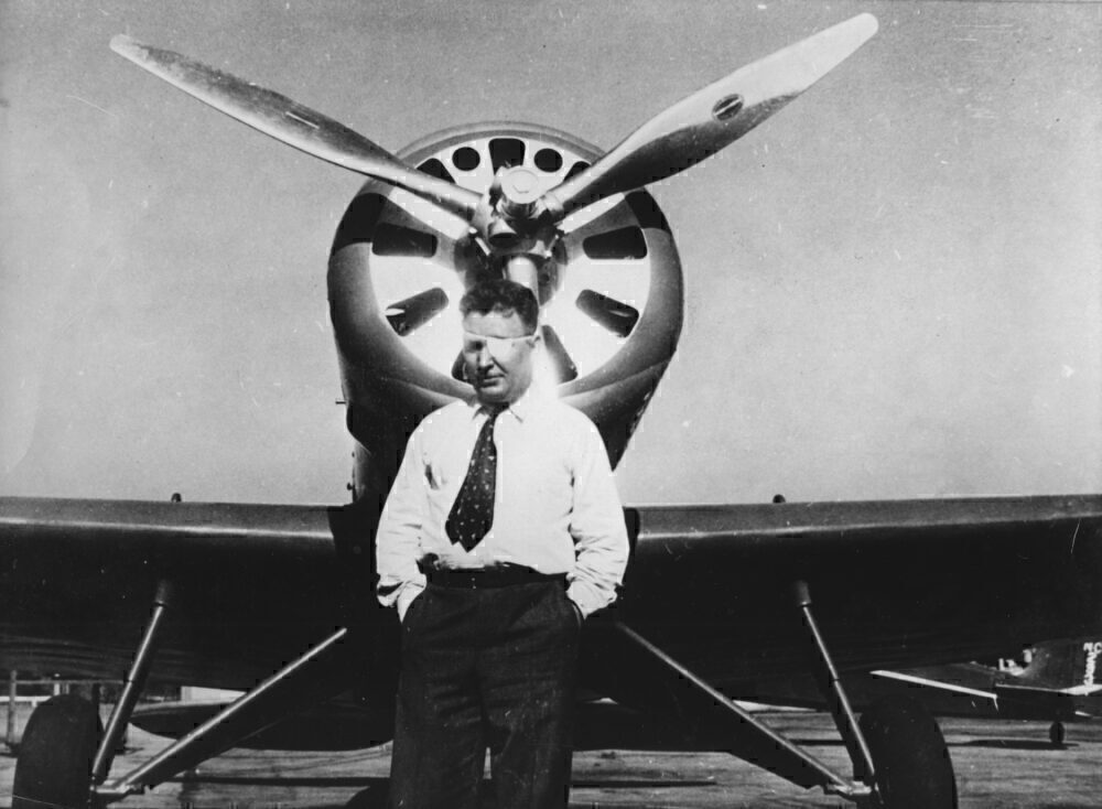 The American Aviator Wiley Post In Front Of His Plane. About 1930. Photograph.