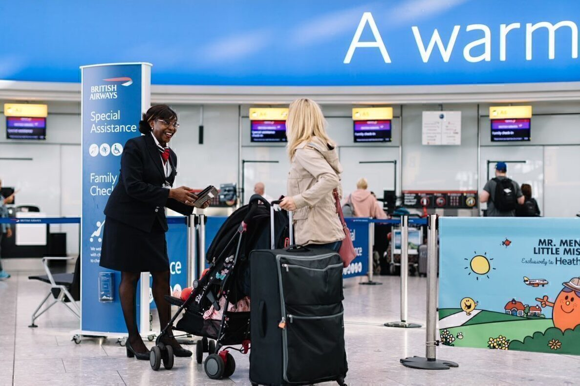 British Airways check in agent greets a passenger with a pram and baggage.