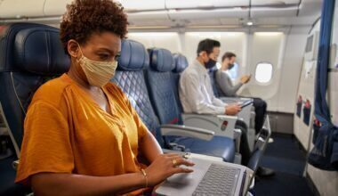 Masked customer in Comfort+ uses laptop inflight during COVID
