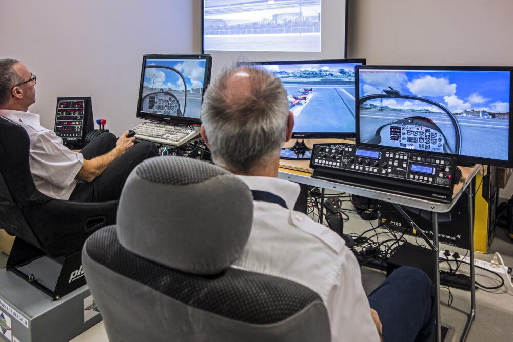 Two men navigating virtual airplane in amateur flight simulator